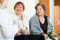 Due pensionati femminili che discutono i problemi sanitari con medico fotografie stock