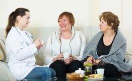 Due pensionati femminili che discutono i problemi sanitari con medico fotografia stock libera da diritti
