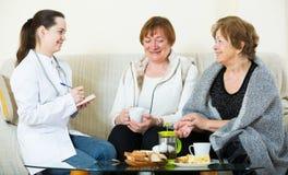 Due pensionati femminili che discutono i problemi sanitari con medico fotografia stock