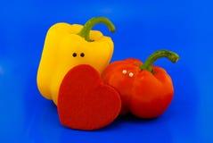 Due peperoni con gli occhi ed il cuore Fotografia Stock