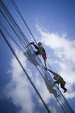 Due persone che arrampicano costruzione fotografia stock