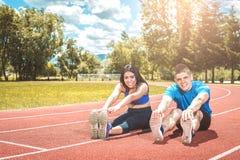 Due persone che fanno allungando esercizio all'aperto Fotografia Stock Libera da Diritti