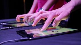 Due persone che giocano musica elettronica con le compresse stock footage