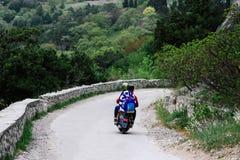 Due persone che guidano una strada della montagna su un motorino d'annata Concettualmente per i viaggiatori e gli amanti dei moto fotografia stock