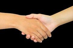 Due persone che stringono le mani su fondo nero Immagini Stock