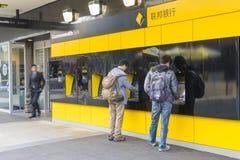 Due persone che usando il ATMs fuori della banca Immagine Stock