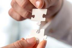Due persone di affari che misura insieme i pezzi di puzzle Fotografia Stock