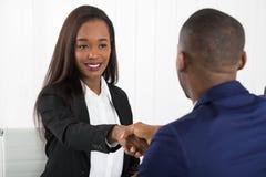 Due persone di affari che stringono le mani all'ufficio Fotografie Stock