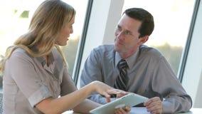Due persone di affari con la compressa di Digital alla riunione stock footage