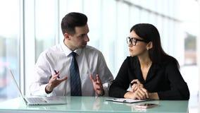 Due persone di affari felici che stanno davanti alle finestre, alla conversazione ed a sorridere dell'ufficio Team il lavoro