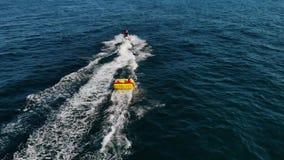 Due persone sulla guida gonfiabile del sofà sulle onde dopo il jet ski Guida del tipo sull'acquascooter con il sofà gonfiabile stock footage