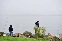 Due pescatori con tre pali lungo il fiume hudson fotografia stock