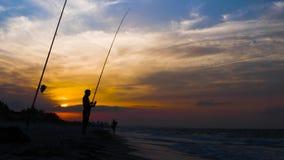 Due pescatori durante la pesca marittima insieme al tramonto, movimento lento stock footage