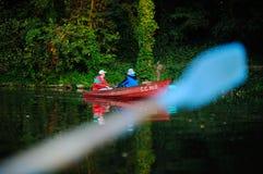 Due pescatori in una barca con le canne da pesca che pescano pesce Immagini Stock