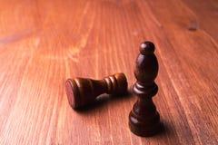 Due pezzi degli scacchi rook e vescovo su un campo di legno, bugie del vescovo supporti di un corvo immagine stock