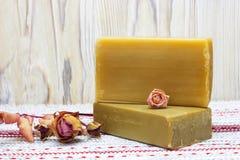 Due pezzi del sapone organico fatto a mano naturale dell'olio d'oliva ed asciugano i fiori ed i germogli rosa sulla tavola di leg Immagini Stock