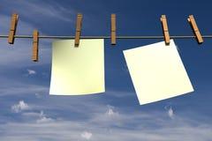 Due pezzi di carta in bianco che appendono su una corda Immagini Stock Libere da Diritti