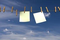 Due pezzi di carta in bianco che appendono su una corda Fotografia Stock