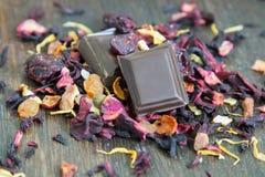 Due pezzi di cioccolato fondente e di foglie di tè sparse Immagini Stock