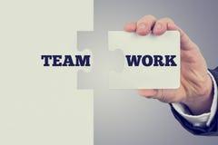 Due pezzi di corrispondenza di puzzle con il lavoro di squadra di parola si diffondono il Th Immagini Stock