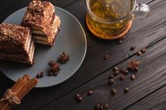Due pezzi di dolce di miele a più strati su un piatto, su un fondo di legno nero con una tazza di tè, dei bastoncini e del caffè Immagine Stock