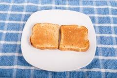 Due pezzi di pane tostato su un piatto bianco. Fotografia Stock