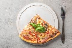In due pezzi di pizza italiana con i pomodori si espande rapidamente il bacon e il che fotografie stock