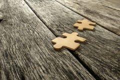 Due pezzi di puzzle che si trovano sui bordi rustici di legno Fotografia Stock Libera da Diritti