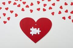 Due pezzi di puzzle collegati bianco sopra cuore rosso Immagini Stock Libere da Diritti
