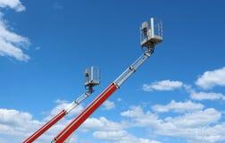 Due piattaforme di lavoro aereo contro cielo blu con le nuvole lanuginose fotografia stock libera da diritti