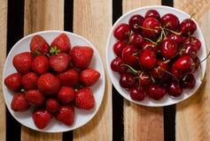 Due piatti con le fragole e le ciliege sui piatti di legno Fotografia Stock