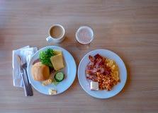 Due piatti della prima colazione con per esempio cresciuto, bacon ed uova rimescolate e caffè con il succo di mele e del latte Immagini Stock Libere da Diritti