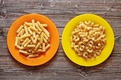 Due piatti di colore con pasta su un fondo di legno immagini stock libere da diritti