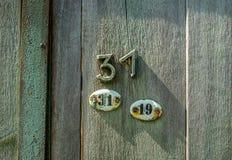 Due piatti di metallo ovali con i nubers trenta uno e diciannove e numero trenta uno inchiodati sulla porta di legno immagini stock