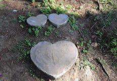 Due piccola pietra della pietra di cuore-forma una grande di forma del cuore e sul punto di via Fotografia Stock