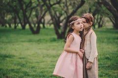 Due piccole amiche felici che selezionano i fiori nel giardino di primavera Sorelle che spendono insieme tempo all'aperto Fotografia Stock