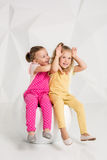 Due piccole amiche nei camici identici dei colori differenti che si siedono su una sedia in uno studio con le pareti bianche Fotografie Stock Libere da Diritti