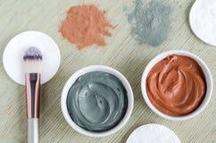 Due piccole ciotole con la maschera cosmetica rossa e grigia dell'argilla Trattamenti casalinghi di bellezza Vista superiore, spa fotografie stock libere da diritti