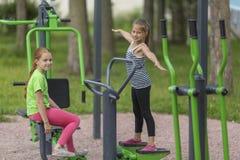 Due piccole ragazze sveglie che si scaldano sul campo da giuoco nel parco Fotografia Stock Libera da Diritti