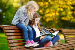 Due piccole scolare adorabili che studiano in una città parcheggiano Fotografie Stock Libere da Diritti
