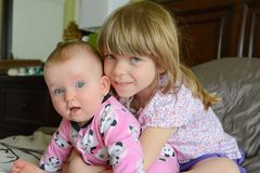 Due piccole sorelle caucasiche adorabili si siedono insieme La sorellina abbraccia la sua bambino-sorella Le ragazze sono sorride immagini stock