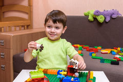 Due piccoli amici caucasici che giocano con i lotti dei blocchi di plastica variopinti dell'interno Ragazzi attivi del bambino, f Fotografie Stock Libere da Diritti