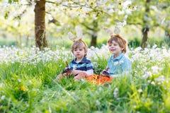 Due piccoli bambini che indossano le orecchie del coniglietto di pasqua e che mangiano chocola immagini stock