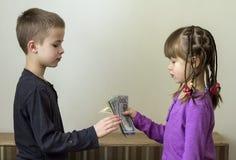 Due piccoli bambini ragazzo e ragazza che giocano con i soldi dei dollari Fotografia Stock Libera da Diritti