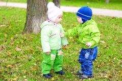 Due piccoli bambini si siedono su uno schiarimento verde Fotografia Stock Libera da Diritti