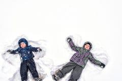 Due piccoli fratelli germani scherzano i ragazzi in vestiti variopinti dell'inverno che fanno la s Fotografia Stock