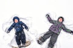 Due piccoli fratelli germani scherzano i ragazzi in vestiti variopinti dell'inverno che fanno la s Immagini Stock Libere da Diritti