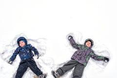 Due piccoli fratelli germani scherzano i ragazzi in vestiti variopinti dell'inverno che fanno la s Immagini Stock