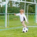Due piccoli giocar a calcioe e calci dei ragazzi del fratello germano sul campo Fotografia Stock