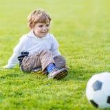 Due piccoli giocar a calcioe e calci dei ragazzi del fratello germano sul campo Immagine Stock Libera da Diritti
